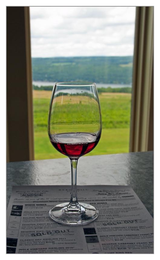 Tasting a glass of Heron Hill 2011 Pinot Noir. Image © Joe Geronimo