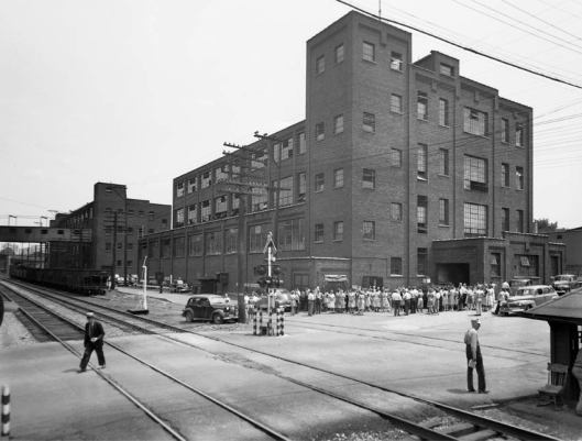 """All Sports Factory"" in foreground at Lackawanna Railroad crossing at Baldwin Street, JC, NY built in 1923. Originally called South End Factory, then the Welt Factory. Ice skates and cleated athletic shoes were the most popular products. The Sunrise Factory can be seen on the left."