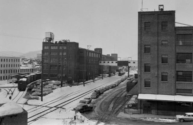 "Looking West along Lackawanna tracks at Willow Street,Johnson City.Sunrise Factory in center completed in 1929 named to suggest a new day coming in the nation. Sunrise produced the all-rubber boots and overshoes for EJ with a walkway across the tracks to the Jigger Factory at right built in 1926, taking its name from the rubber-soled canvas-topped footwear called ""Jiggers. Both factories initially used a common labor force of some 400 employees. In the summer,Sunrise workers produced foot-wear for winter use; in the winter, the same workers moved to the Jigger factory and produced footwear for summer use. Jigger was demolished in February 2012. Light factory at the left was the Fair Play Caramel Company."