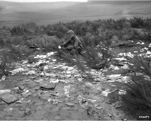 Mailing to the frontlines: American soldier finds lost letters near Auw, Germany; February 1945. National Archives (111-SC-200677).