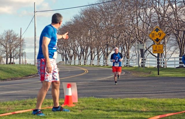 Team Captain Joe Geronimo anticipates the handoff from Rick Bennett at milepost 74.3. Only 3.7 miles to the finish. Image © Chris Strub