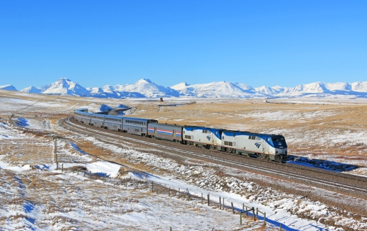 "Amtrak train No. 8 the ""Empire Builder"" with Glacier National Park in the distance. Photo by: Justin Franz."