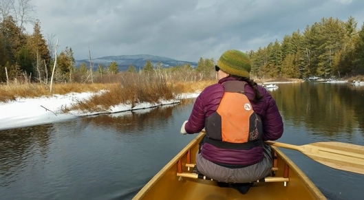Chad Smith and his Wife Emily paddle their canoe along Minerva stream in the Adirondacks on January 1st 2016.