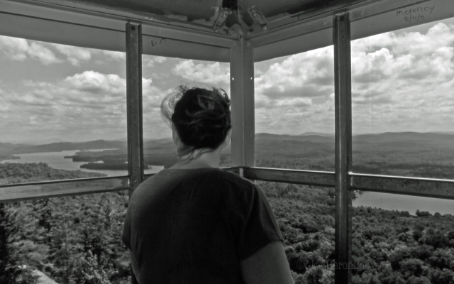 My wife peers from the cabin of the Rondaxe fire tower. © Joe Geronimo